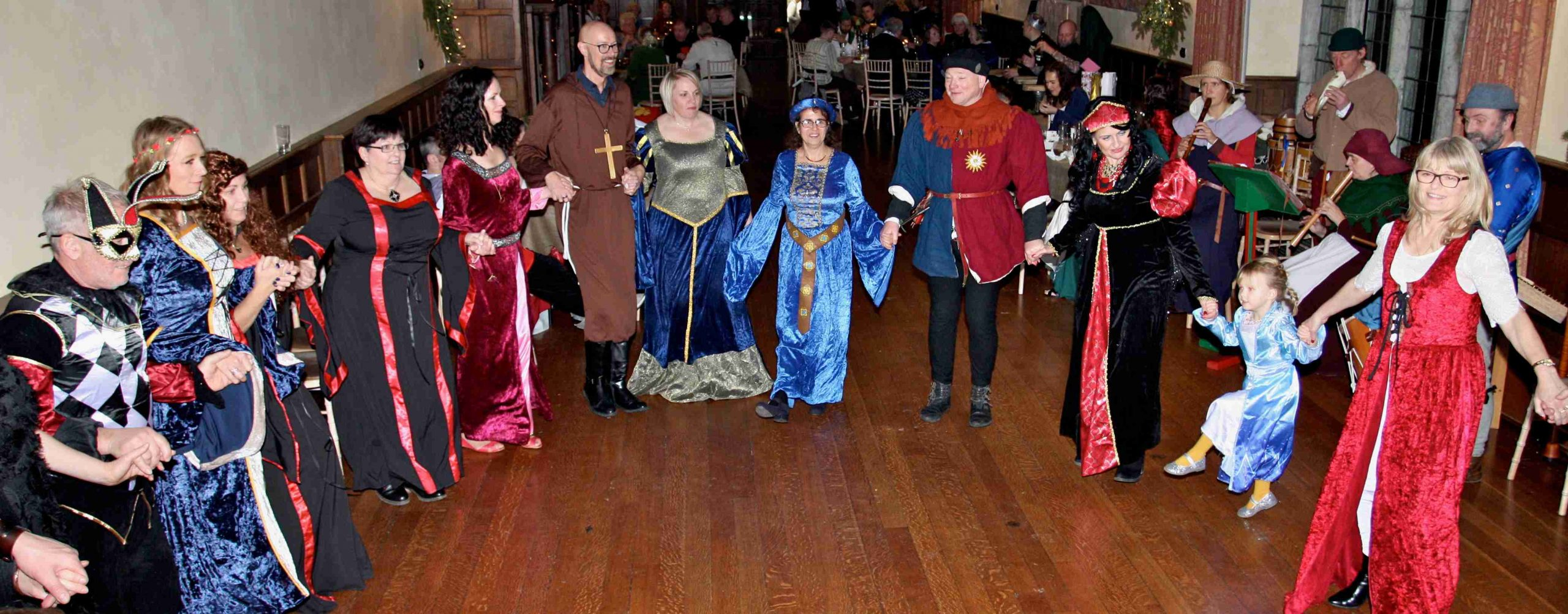 Guests dancing in reception room, medieval theme party