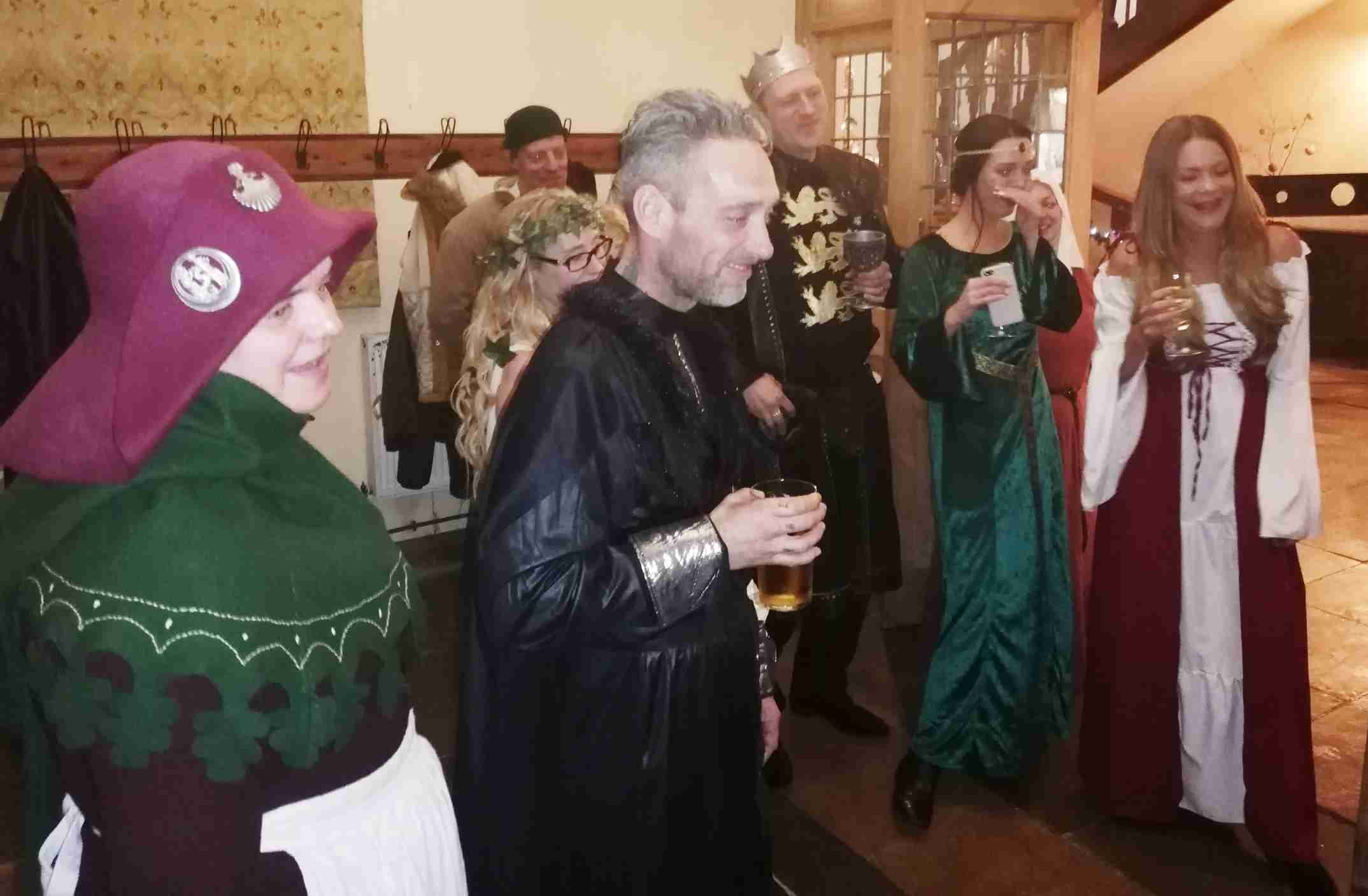 Party guests in medieval costume waiting to apple bob