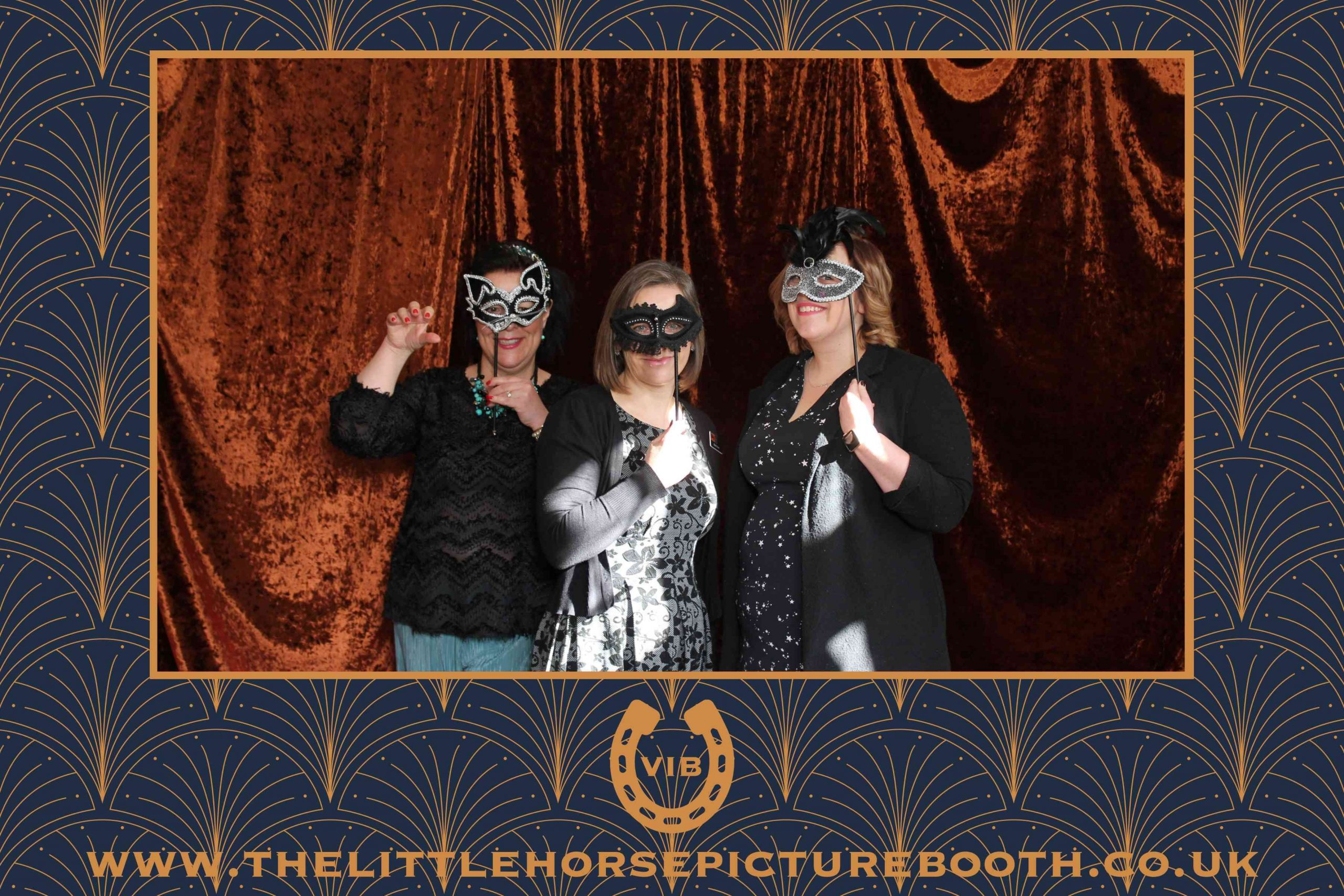 People wearing masquerade ball masks in photobooth