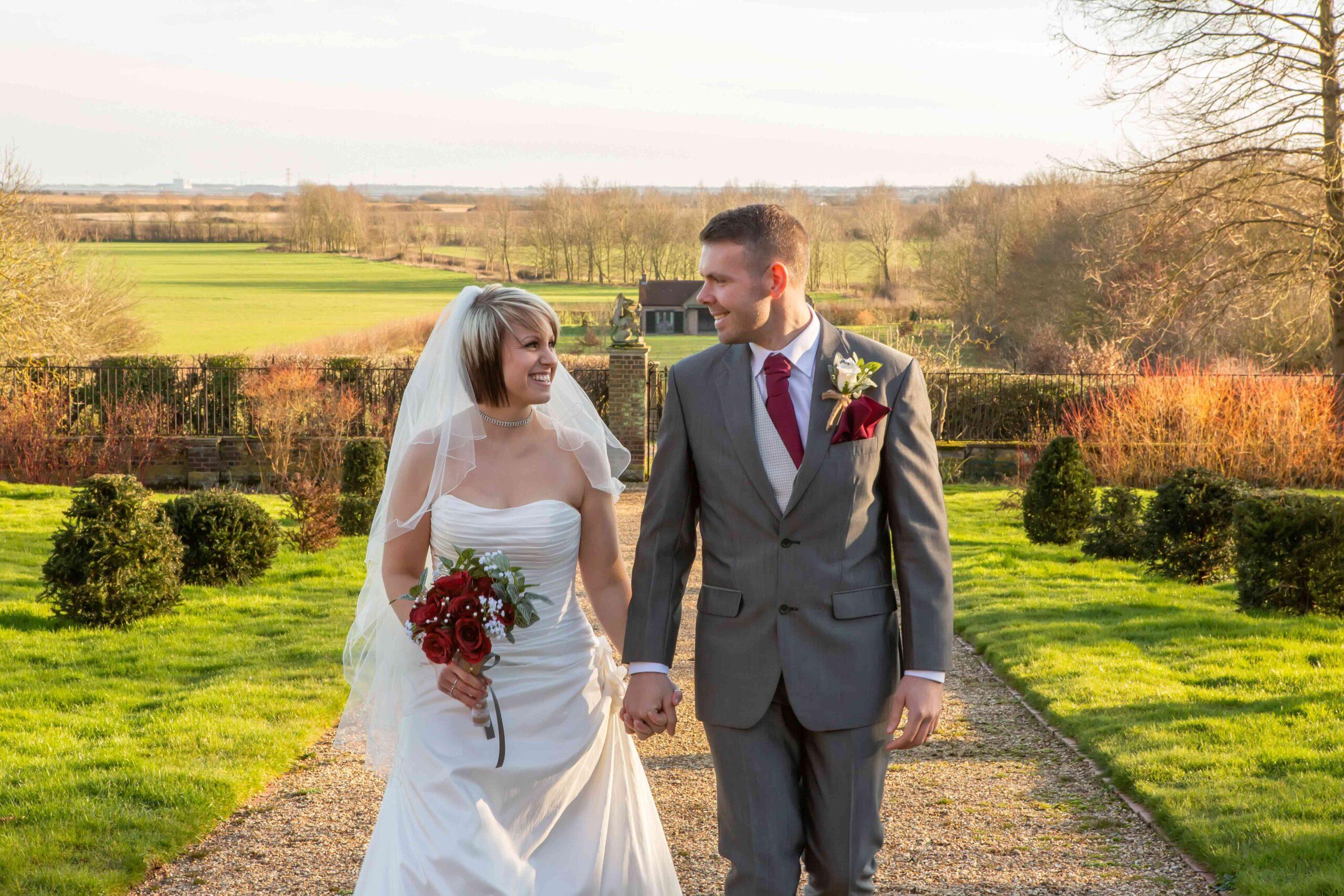 Bride and Groom walking through the garden towards the Tudor tower