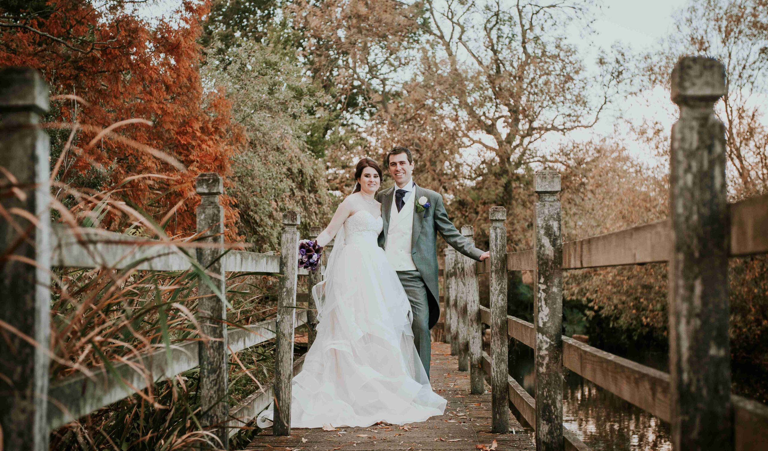 Bride and groom pictured on the boardwalk around pond