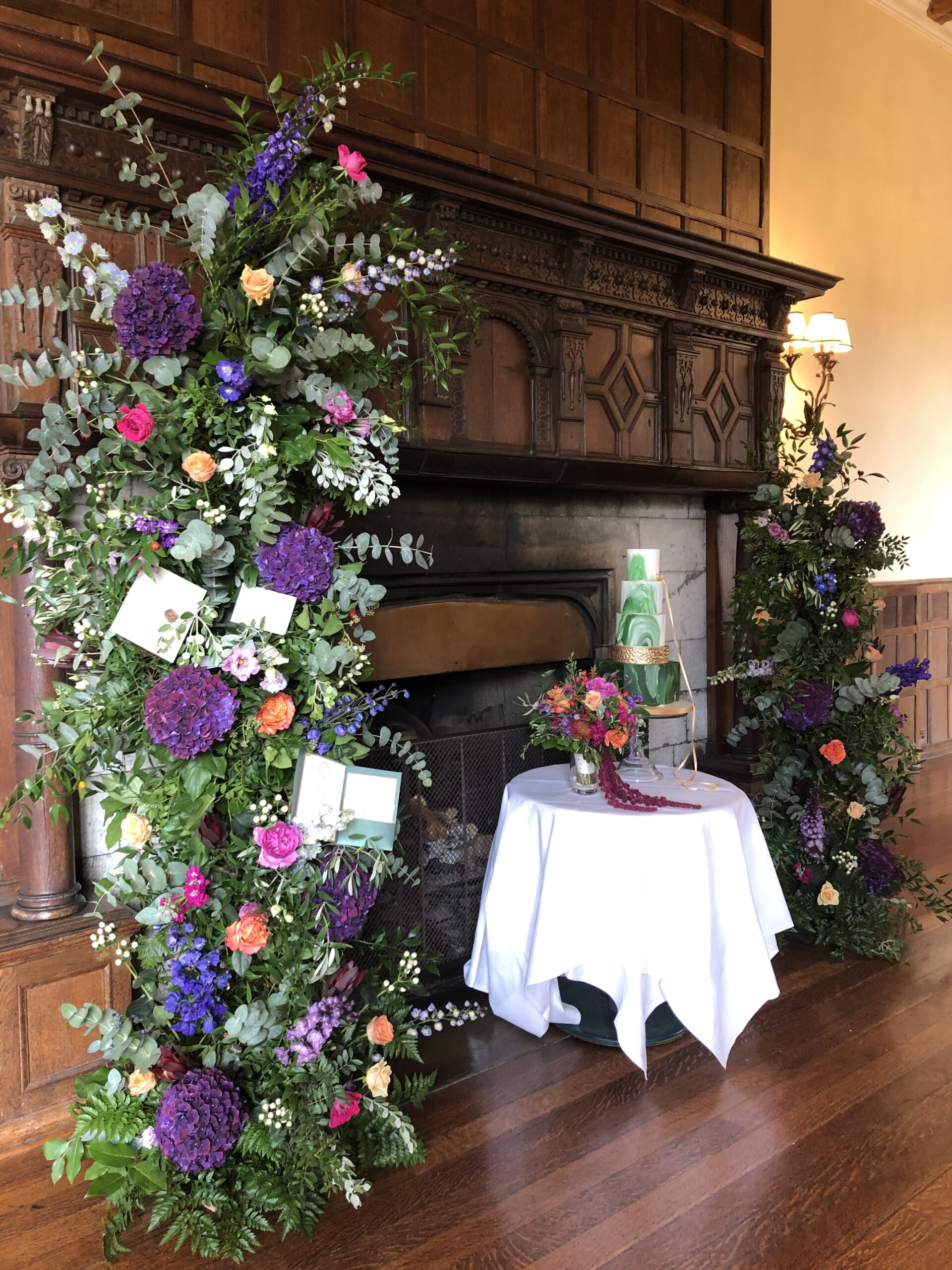 Fireplace surrounded by flowers, wedding cake