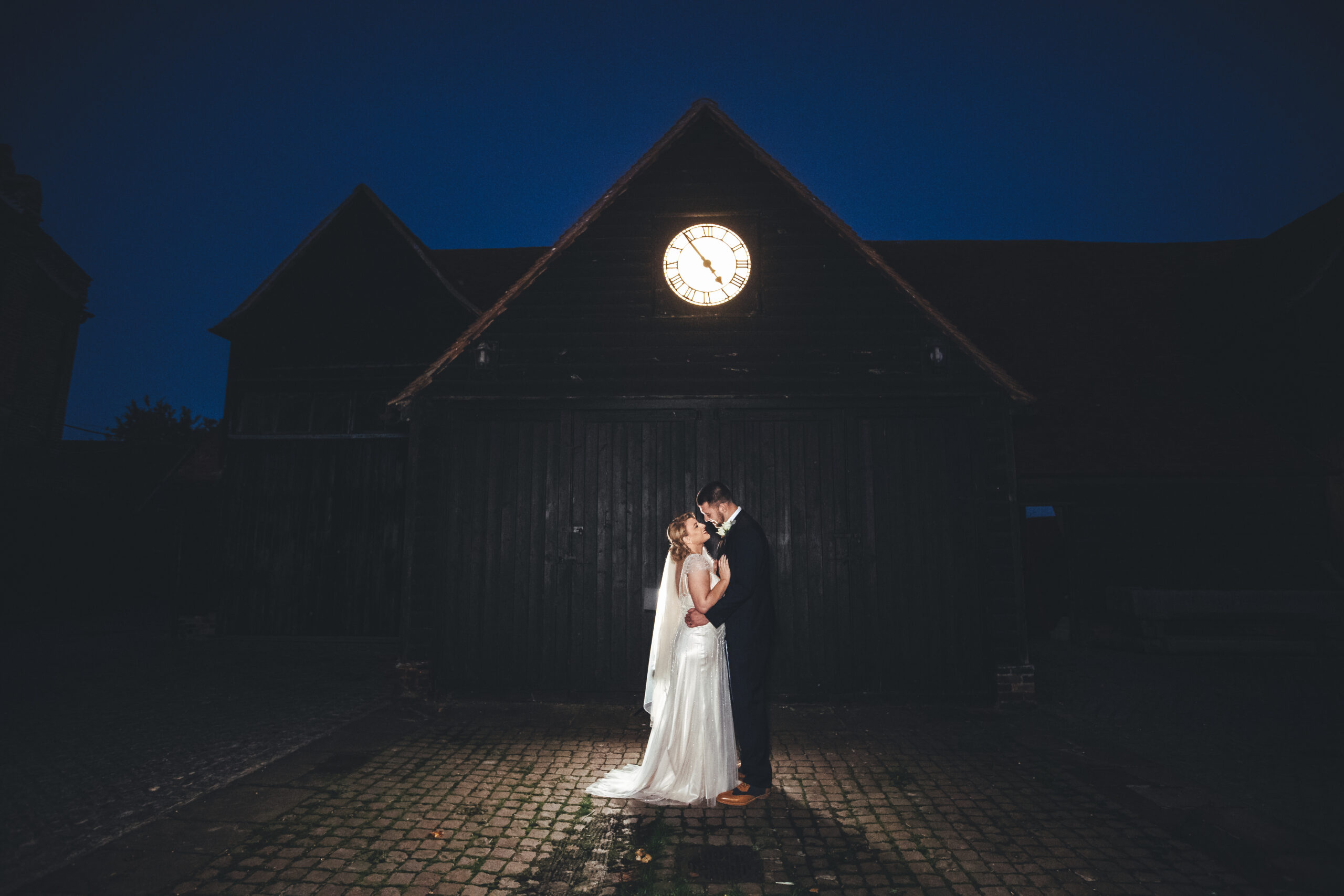 Bride and groom outside barn at night