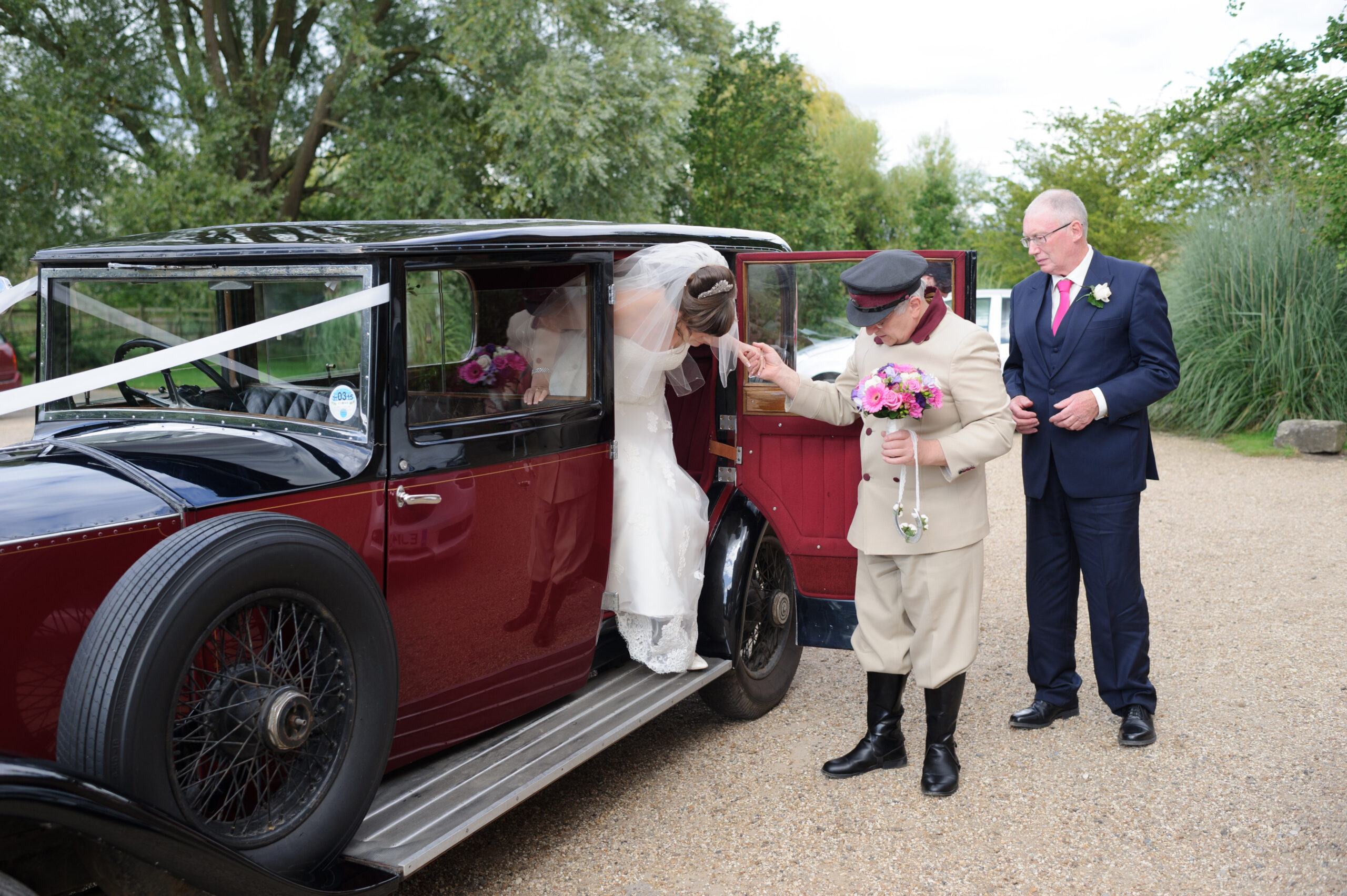 Chauffeur offering bride a hand out of the Rolls Royce