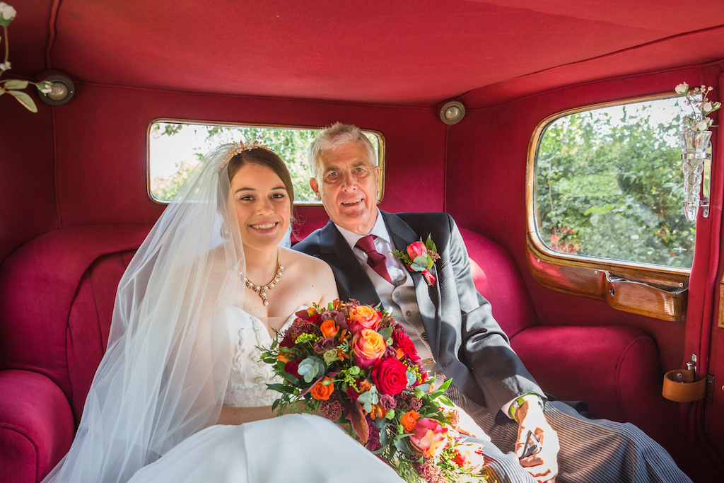 Bride with father arriving in wedding car