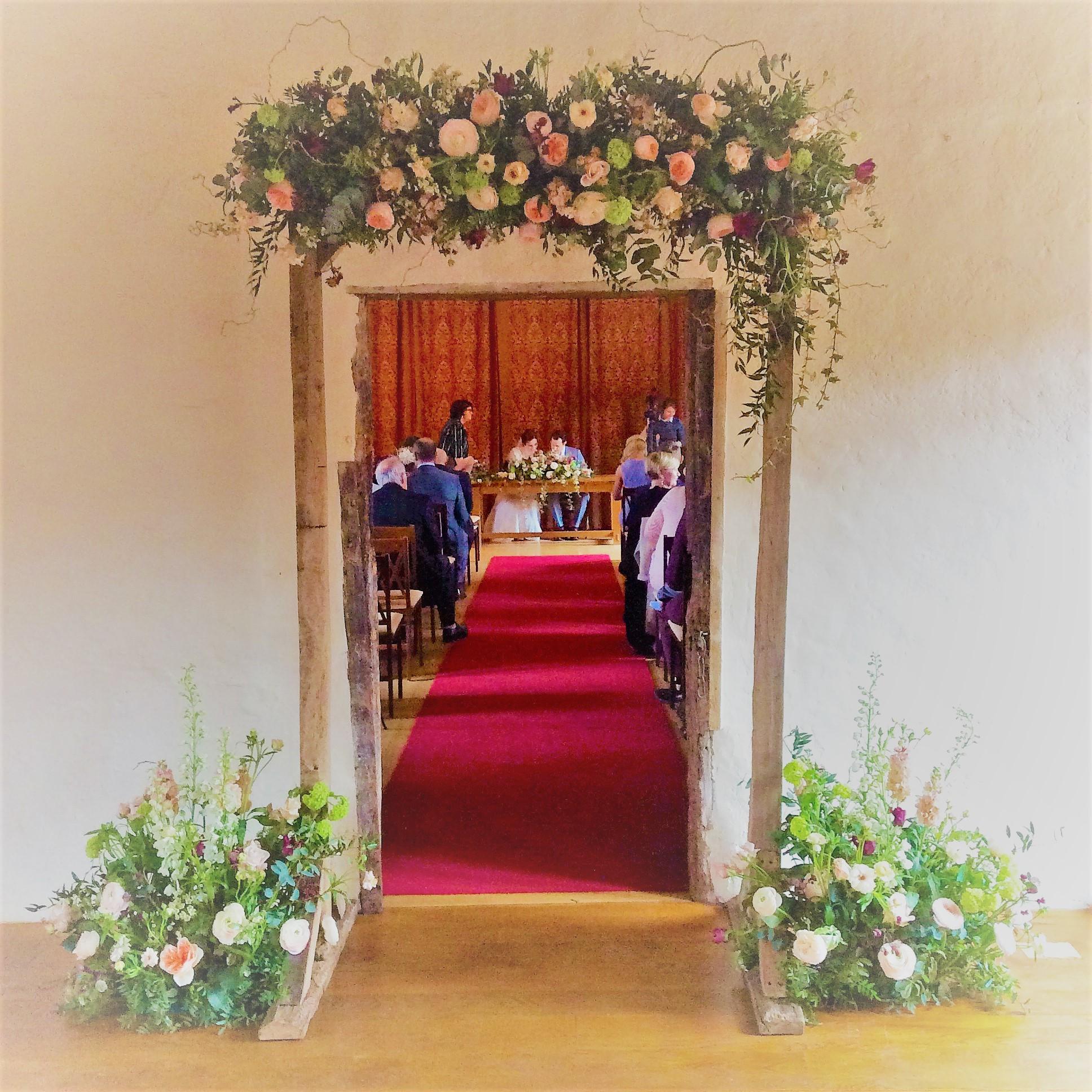 Floral archway into wedding ceremony room