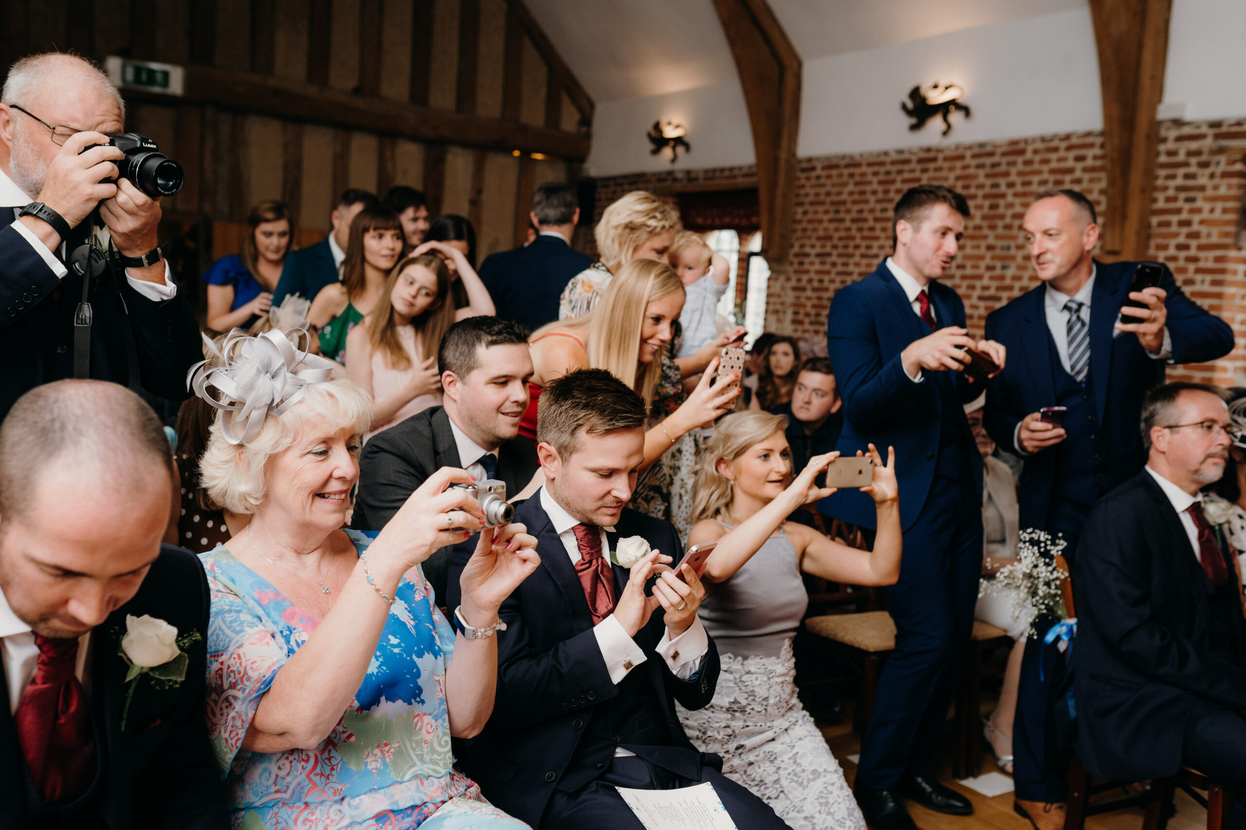 Wedding guests taking a photo of the bride and groom