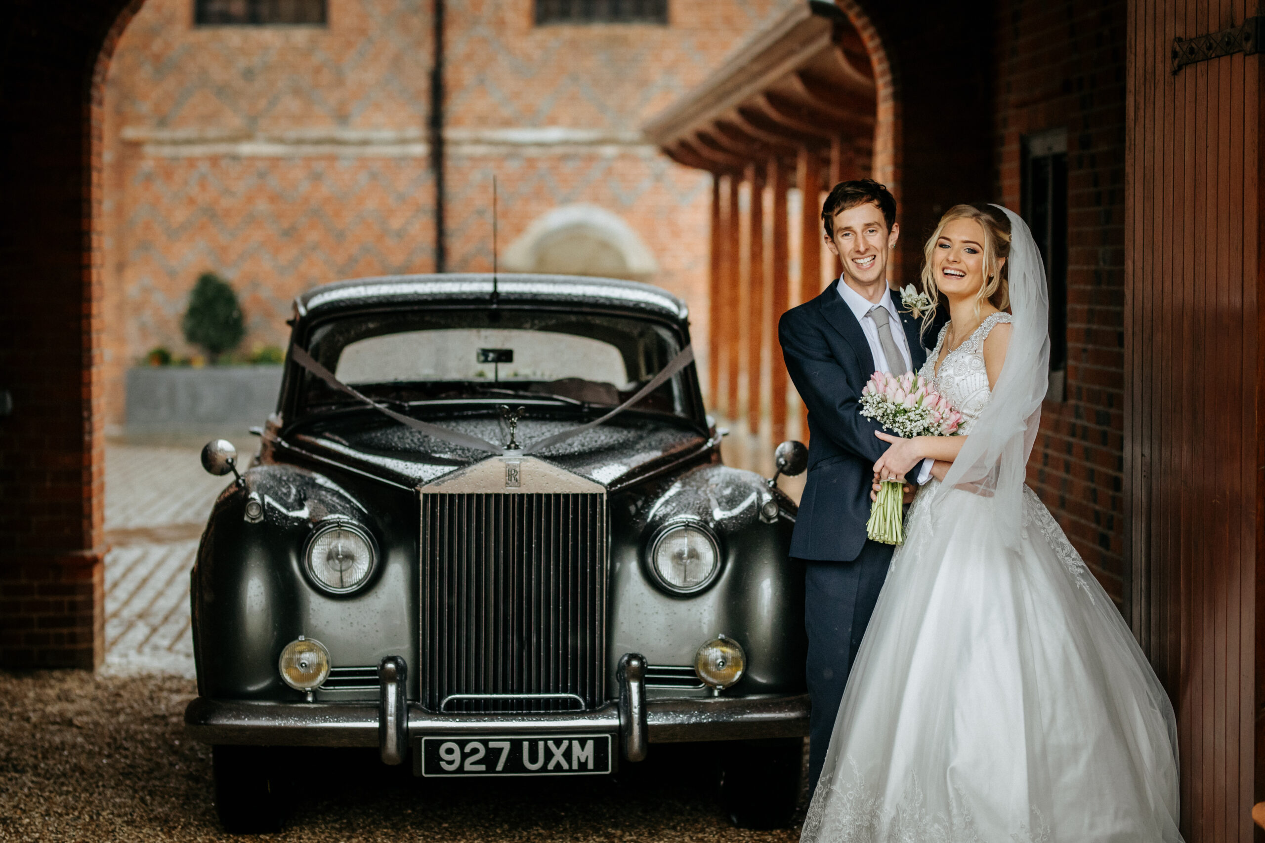 Bride and Groom with Silver Cloud sheltering from rain