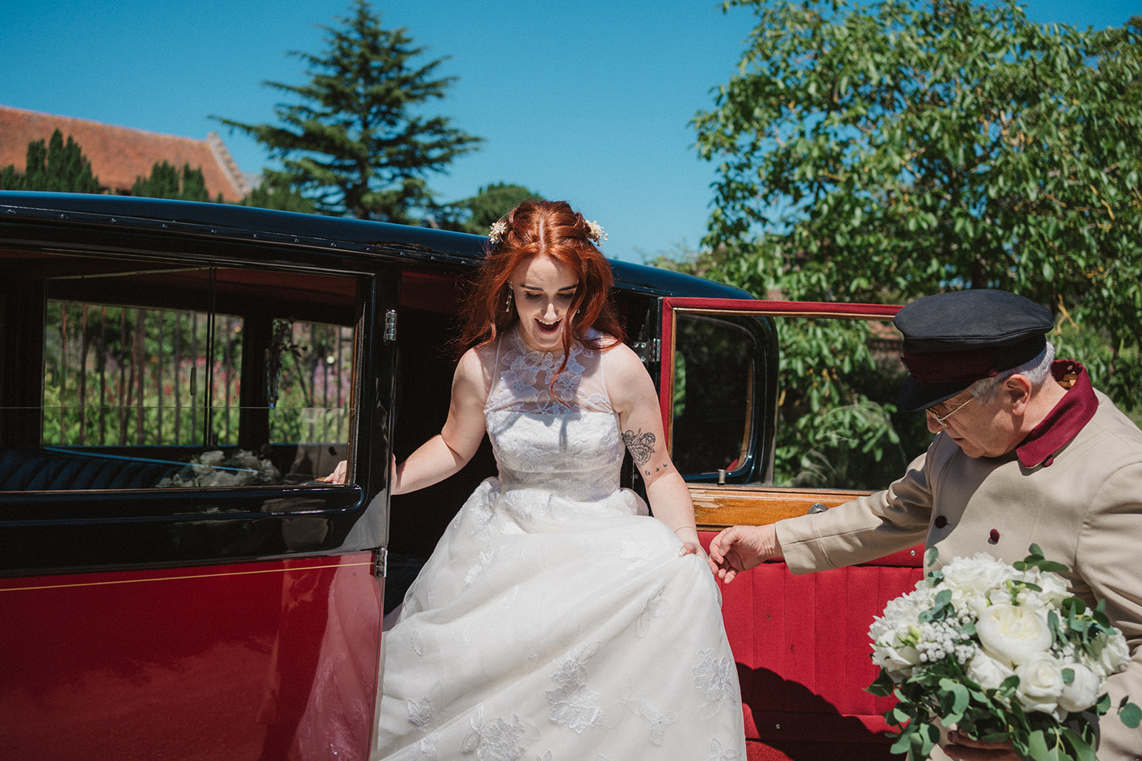 The bride being helped out of the wedding car by the chauffeur